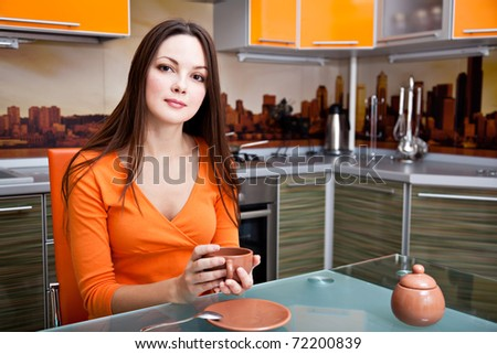 a young beautiful woman is drinking in the kitchen - stock photo