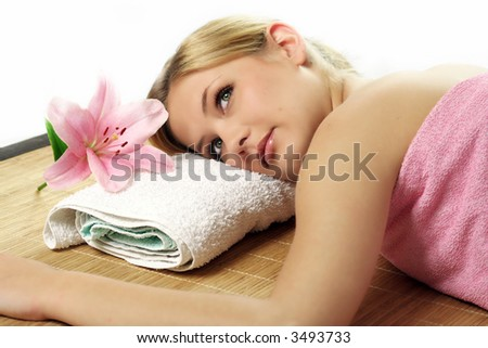 a young beautiful woman is relaxing in spa - wellness with a flower lily
