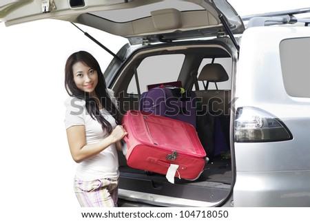 A young beautiful woman prepares her luggage for traveling - stock photo