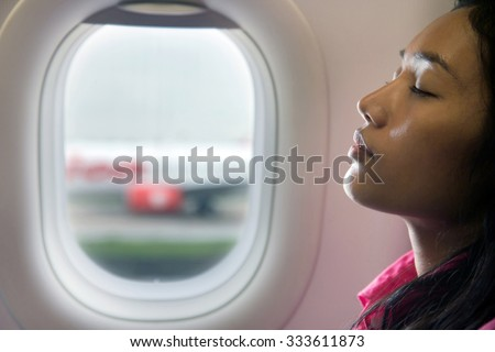 A young beautiful woman resting on airplane beside window. Portrait of a woman sitting on a plane next to a window. Passenger relaxes on takeoff. The traveler sleeps in the plane after landing.