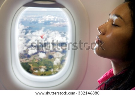A young beautiful woman resting on airplane beside window. Portrait side view of passenger sleeping in the aircraft.  Woman flying on a air plane at a window overlooking the countryside with clouds. - stock photo