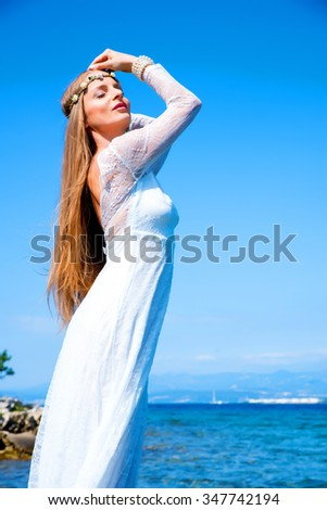A young beautiful woman standing at the ocean in the summer. - stock photo