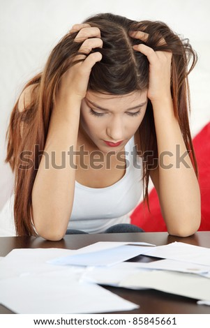 A young beautiful woman stressed because of bills. - stock photo