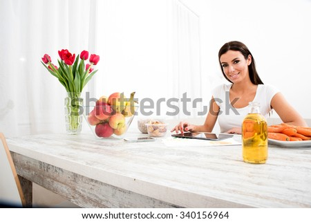 A young beautiful woman using a Tablet computer at home in the kitchen.  - stock photo