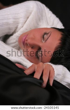 A young beautiful woman wearing  white sweater lying on the bed covered with black cloth - stock photo