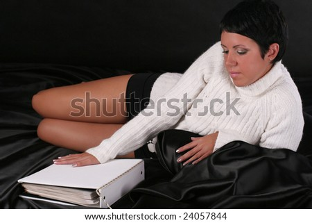 A young beautiful woman wearing white sweater lying on the bed covered with black cloth near the white photo-album - stock photo