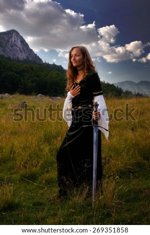 A young beautiful woman with blonde hair in historical dress is posing in an enchanting open landscape with trees and a mountain meadow, with a hand-to-heart gesture and mystical medieval sword. - stock photo