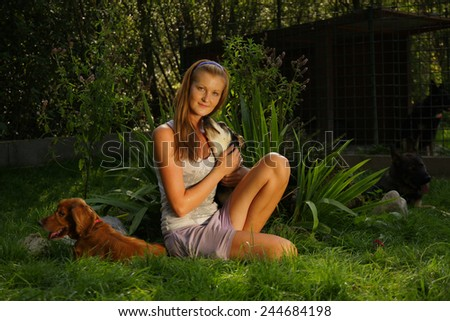 A young beautiful woman with blonde hair is holding lovingly a stray dog in her arms  sitting in a backyard garden with green grass profile portrait eye contact  - stock photo