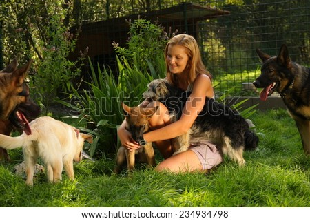 A young beautiful woman with blonde hair is playing lovingly with a bunch of dogs in a backyard garden with green grass
