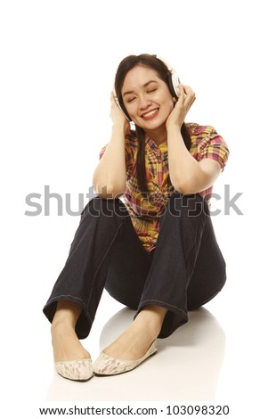 A young beautiful woman with headphones enjoying the music (on white background)