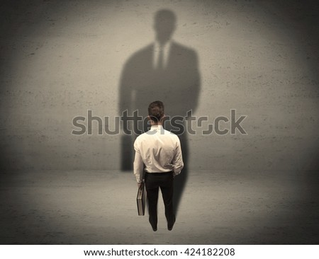 A young beginner salesman standing in front of a wall, facing his shadow as his boss or a successful businessman he lloks up to concept - stock photo