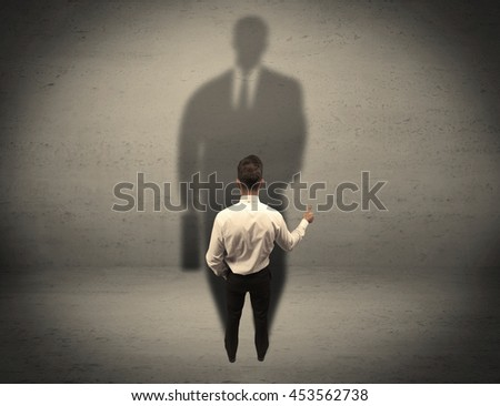 A young beginner salesman standing in front of a wall, facing his shadow as his boss or a successful businessman he looks up to concept - stock photo