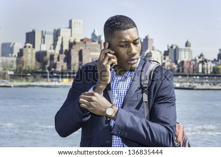 A young black businessman is on the phone, traveling by a river./Portrait of Businessman - stock photo