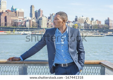 A young black businessman is standing by the river, looking forward. Background is a old big city scene. / Traveling