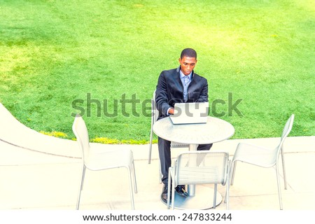 A young black college student is sitting by green lawn on campus, looking down, working on a laptop computer, connected with wireless Internet. Concept of modern life, technology and environment.  - stock photo