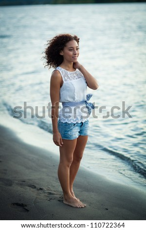A young black woman stands on a beach by a river. - stock photo