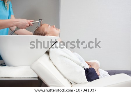 A young blond caucasian woman having her hair washed and rinsed at a beauty salon.