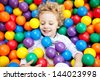 A young blond girl child having fun playing with colorful plastic balls - stock photo