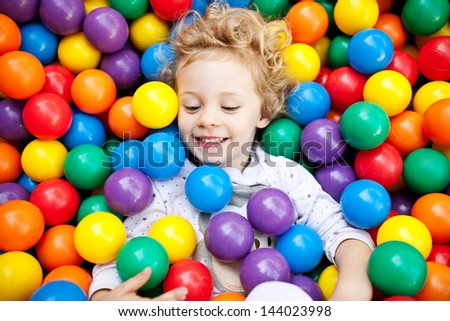 A young blond girl child having fun playing with colorful plastic balls