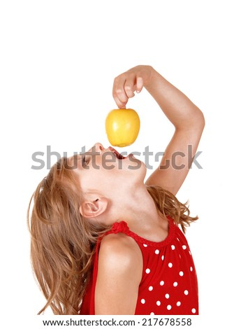 A young blond girl is playing with her yellow apple she likes to eat, isolated on white background.  - stock photo