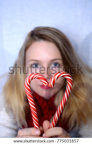 A young blond woman with two candy canes forming a heart. The woman is out of focus