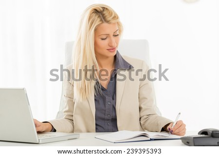 A young blonde businesswoman sitting at an office desk in front of a laptop and writing in planner with the left hand.
