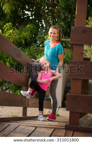 A young blonde daughter and her mother are standing together on a wooden bridge, smiling and happy. They are both wearing fitness gear and are about to go run and play on the beach.