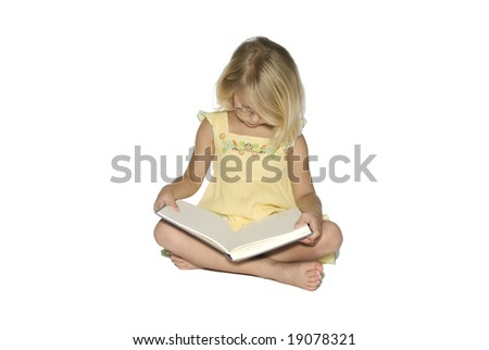 A young blonde girl sitting crosslegged while reading a textbook.  Isolated on a white background