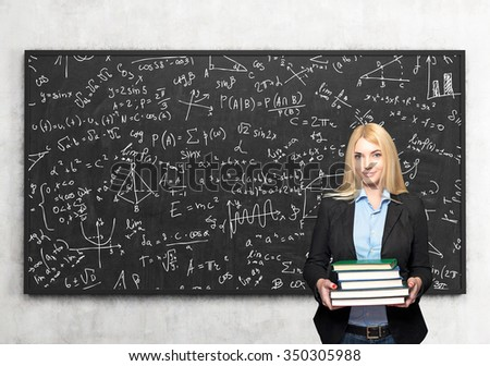 a young blonde girl standing and holding books, blackboard with small signs and dawings at the background, a concept of studying and knowledge aquisition
