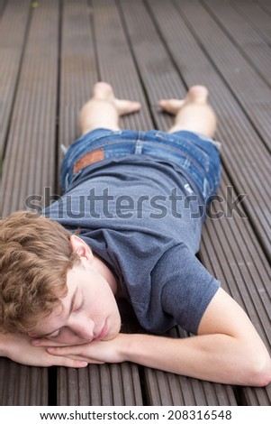 A young blonde male model is sleeping peacefully on a dark wooden background