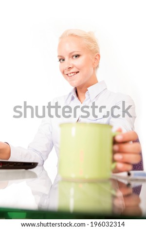 A young blonde secretary holding a cup of coffee on the desk isolated on white. - stock photo