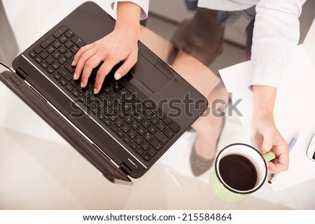 A young blonde secretary holding a cup of coffee seen from above the desk .  - stock photo
