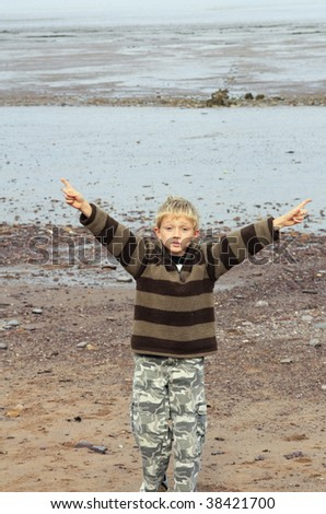 a young blonde seven year old boy playing on the beach