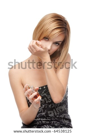 a young blonde woman holding a bottle of perfume in one hand and smelling the fragrance on the othe hand's wrist. - stock photo