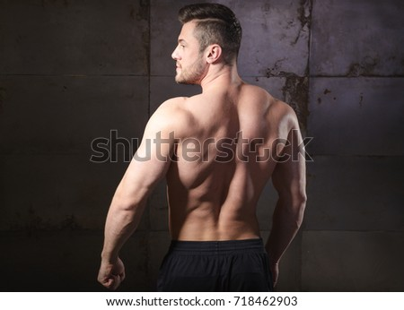 A young bodybuilder stands with his back and shows muscles. Body. Healthy lifestyle. Trainer. Energy