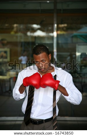 a young boxer poses with his boxing gloves for the press before the big fight - stock photo