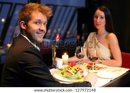 A young boy and a beautiful girl having dinner - stock photo