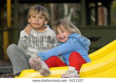 a young boy and girl sit together on the playground