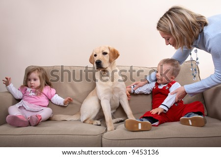 A young boy and girl with Downs Syndrome at a dog therapy session with mom - stock photo