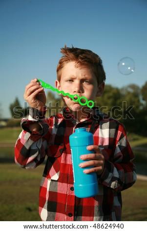 a young boy blows bubbles - stock photo