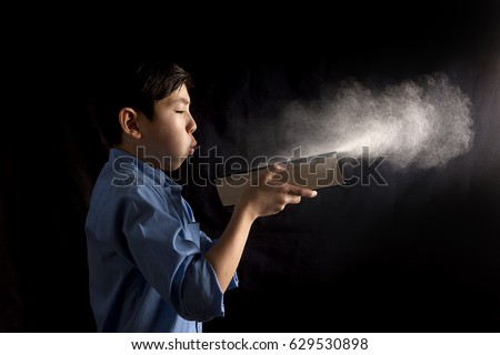 A young boy blows dust off a book in this conceptual image.