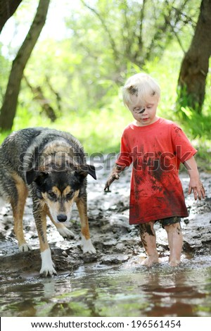 A young boy child and his German Shepherd mix dog are covered in mud and playing outside on the beach of a river in the woods. - stock photo