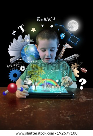 A young boy child is looking at a computer tablet with math, science and animals around him on a black background for a school learning or technology concept. - stock photo