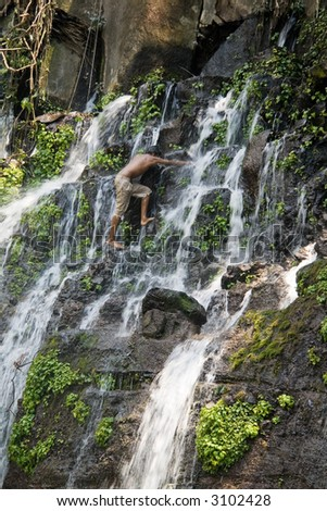 A young boy climbing up a jungle waterfall