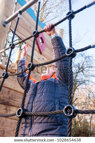 A young boy climbing up a rope ladder on a climbing frame in a park