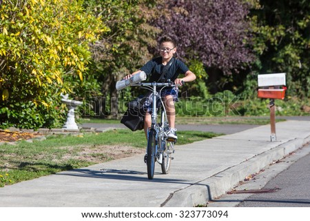 A young boy delivering newspapers on his bicycle - stock photo