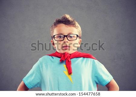 A young boy dreams of becoming a superhero. - stock photo