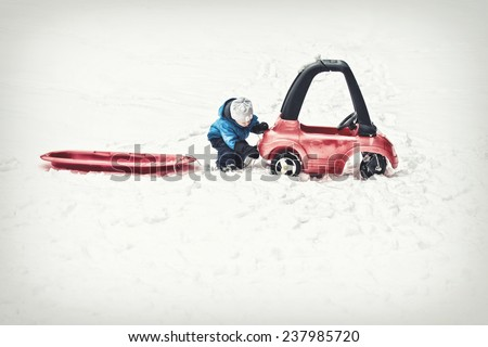 A young boy dressed for cold weather attaches a red sled with a rope to his toy car during the winter season.  Filtered for a retro, vintage look.  - stock photo