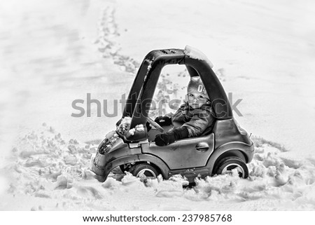 A young boy dressed for cold weather sits in a red toy car stuck in the snow during the winter season.  Processed in black and white.  Filtered for a retro, vintage look.  - stock photo