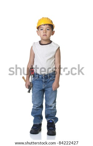 A young boy dresses up in construction cloths with some tools. - stock photo